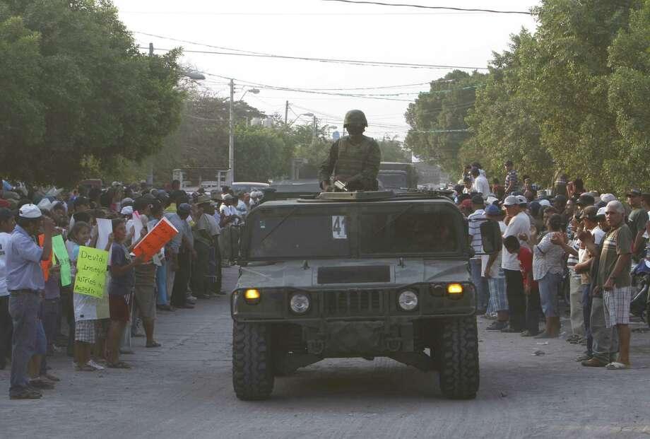 Los residentes saludan a soldados en la entrada de  La Ruana, Michoacan, México. Los residentes se unieron para combatir a los narcotraficantes y otros criminales. Photo: Associated Press