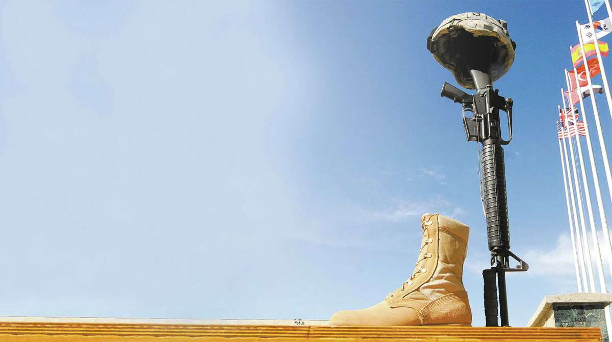 A rifle, helmet and pair of boots are positioned as a token of respect during a Memorial Day ceremony at Bagram Air Base in Afghanistan in 2009.