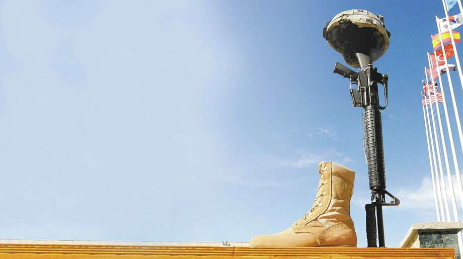 A rifle, helmet and pair of boots are positioned as a token of respect during a Memorial Day ceremony at Bagram Air Base in Afghanistan in 2009. Photo: Getty Images