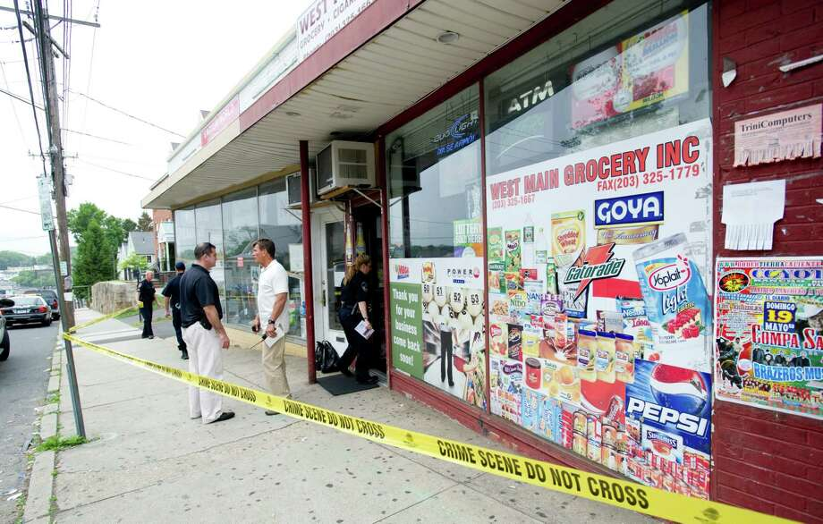 Police officers work at the scene of an armed robbery at West Main Grocery Inc. in Stamford, Conn., on Wednesday, May 22, 2013. Photo: Lindsay Perry / Stamford Advocate