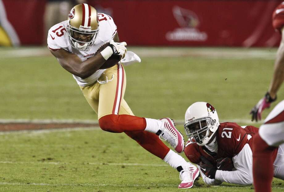 San Francisco 49ers' Michael Crabtree (15) breaks away from Arizona Cardinals' Patrick Peterson (21) after making a catch during the first half of an NFL football game Monday, Oct. 29, 2012, in Glendale, Ariz.