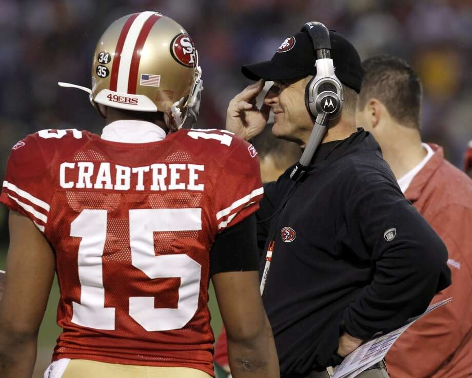 Jim Harbaugh speaks with reciever Michael Crabtree on the sidelines.