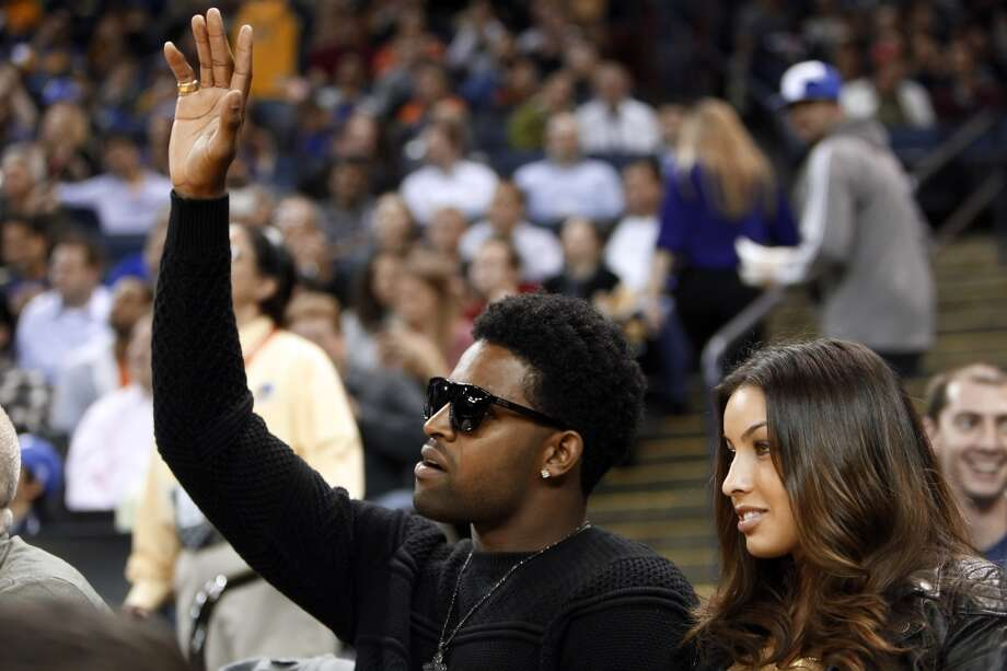 49ers wide reciever Michael Crabtree acknowledges the crowd as he watches the Warriors game in the first half. The Golden State Warriors played the Denver Nuggets at Oracle Arena in Oakland, Calif., on Thursday, November 29, 2012.