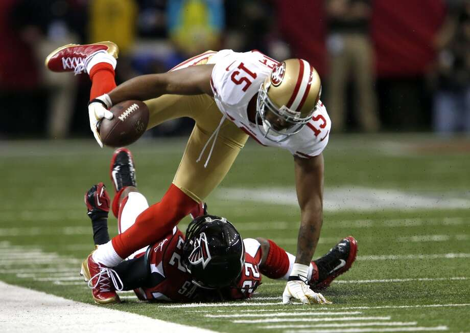 Wide receiver Michael Crabtree runs over Falcons cornerback Asante Samuel during the first half of the San Francisco 49ers game against the Atlanta Falcons in the NFC Championship game.