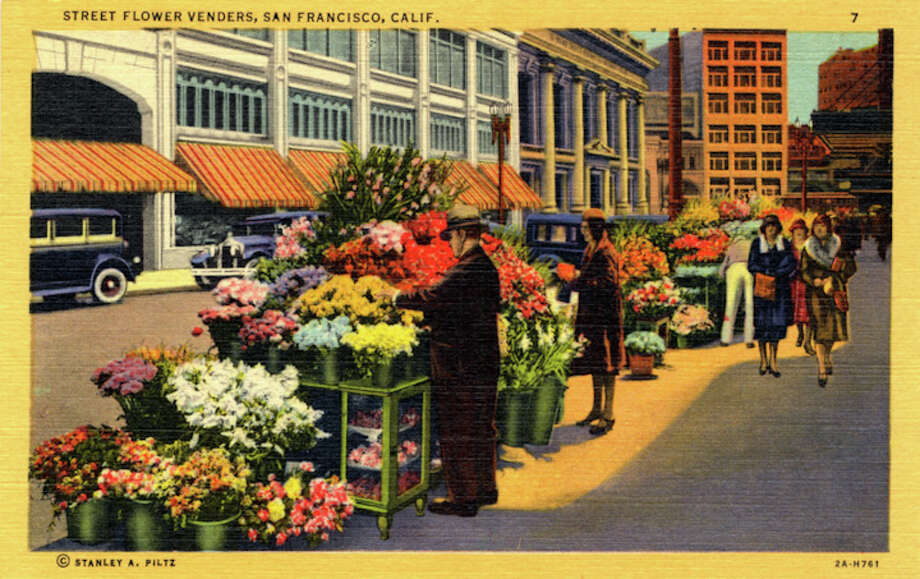 Vintage linen postcard showing the flower vendors selling flowers from their stalls on the street. Pedestrians walk by and city buildings are visible across the street. Photo: Getty Images / Curt Teich Postcard Archives
