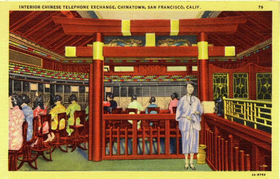 Vintage linen postcard showing the interior of the telephone exchange were women sit at switchboards and another woman stands in the foreground.  Photo: Getty Images / Curt Teich Postcard Archives