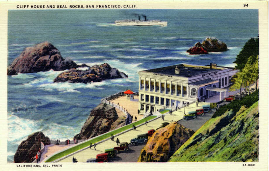 Vintage linen postcard showing a bird's eye view of the Cliff House and Seal Rocks. Vintage automobiles line the parking areas and pedestrians walk on a sidewalk along the shore. A ship is seen in the ocean in the distance. Photo: Getty Images / Curt Teich Postcard Archives
