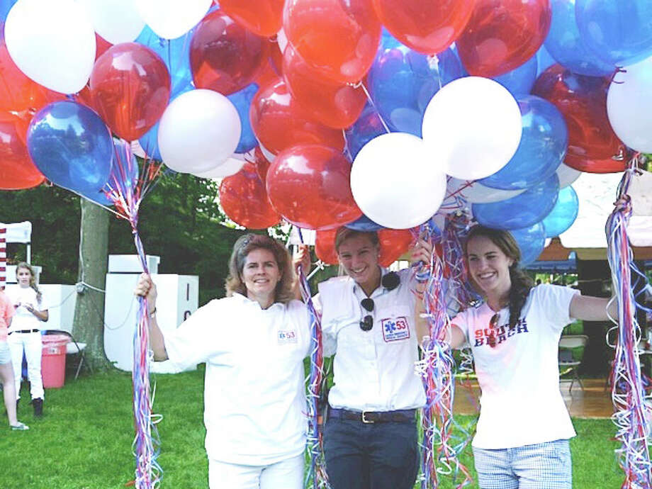 Jen Robinson, Lilly Cassidy and Maggie Close arrange balloons at Tilley Pond Park during last year's Darien EMS-Post 53 annual Food Fair. Photo: Contributed Photo