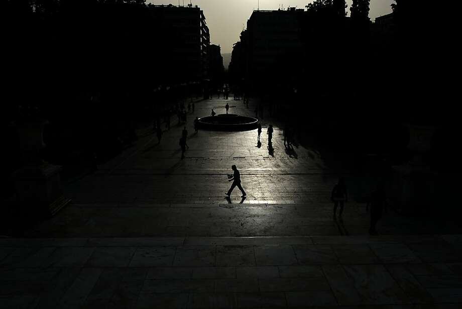 TOPSHOTS People walk at the Athens' main square of Syntagma on May 21, 2013. AFP PHOTO / ARIS MESSINISARIS MESSINIS/AFP/Getty Images Photo: Aris Messinis, AFP/Getty Images
