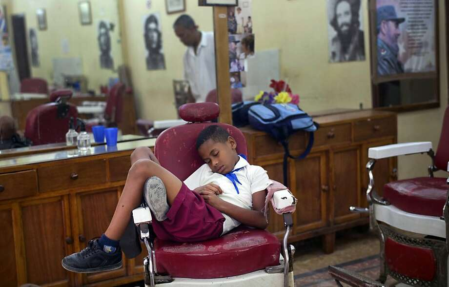 Shear exhaustion:Seven-year-old Jose Luis falls asleep in a barber's chair while waiting for his father's shift to end in Old 