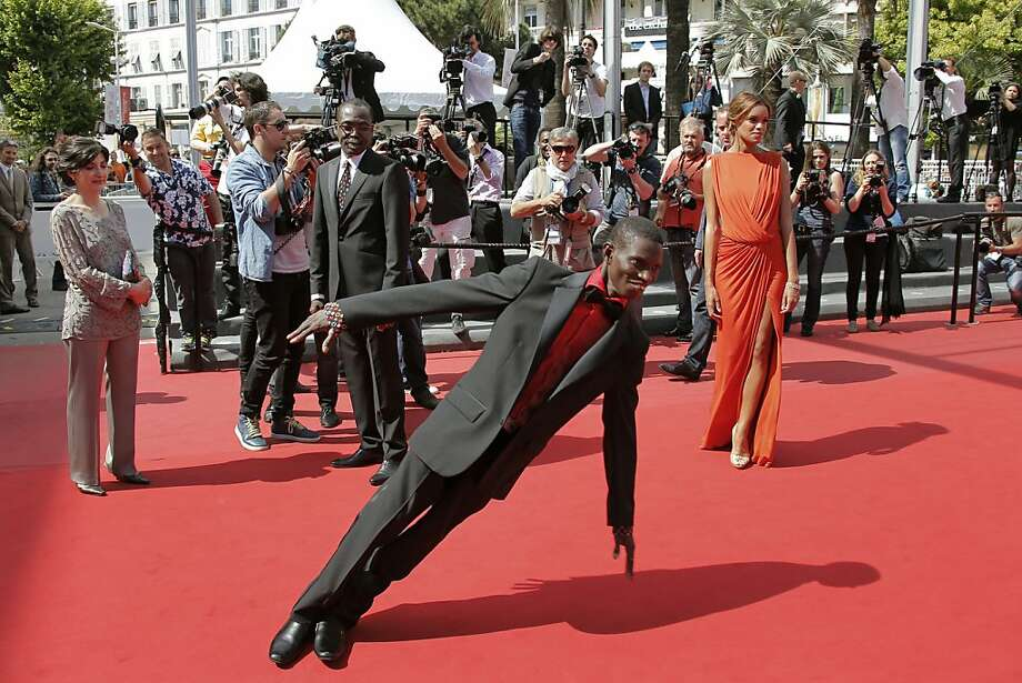 Actor Souleymane Deme, foreground, performs a dance as producer Florence Stern, left, director Mahamat-Saleh Haroun, rear centre, and actress Anais Monory, right, watch him as they arrive for the screening of Grigris at the 66th international film festival, in Cannes, southern France, Wednesday, May 22, 2013. (AP Photo/Lionel Cironneau) Photo: Lionel Cironneau, Associated Press