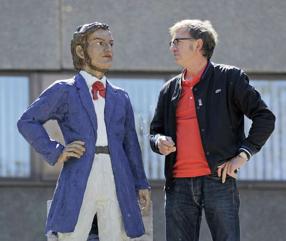 FILE - In this May 15, 2013 file photo German artist Stephan Balkenhol, right, stands besides a part of  his  Richard Wagner Monument during the installation in Leipzig, central Germany. The Wagner monument will  be unveiled Wednesday, May 22, 2013, to celebrate the German composer's 200th birthday. It shows a young Wagner overshadowed by his older, famous self. Some of Wagner's works will be performed later in the day in Bayreuth, where the composer's descendants organize an annual music festival. (AP Photo/Jens Meyer, File) Photo: Jens Meyer