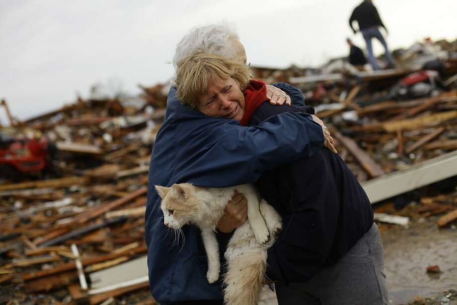 Amid the devastation, a survivor:June Simson holds Sammi and hugs neighbor Jo McGee after finding the cat standing   in the rubble of her destroyed home in Moore, Okla. The monster tornado that hit Moore flattened entire neighborhoods, often leaving nothing but foundations and piles of rubble. Photo: Joshua Lott, AFP/Getty Images