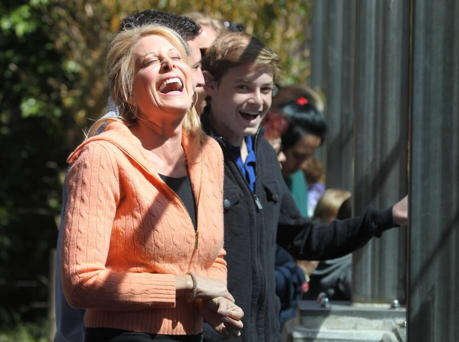 Jillian Manus from Atherton Calif, and her two sons Nick Salzman 18 and Brock Salzman 14 react after seeing the baby tiger cub emerge from the den at the San Francisco Zoo Wednesday, May 22, 2013 in San Francisco. Manus paid $47,000 for the privilege of naming the cub Jillian.