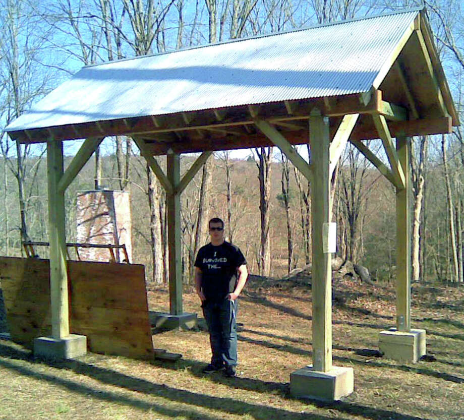 Scott Irwin of Roxbury stands proudly with the structure he built as his Eagle Scout project at the Mine Hill Preserve in Roxbury. May 2013  Courtesy of the Irwin family Photo: Contributed Photo / The News-Times Contributed