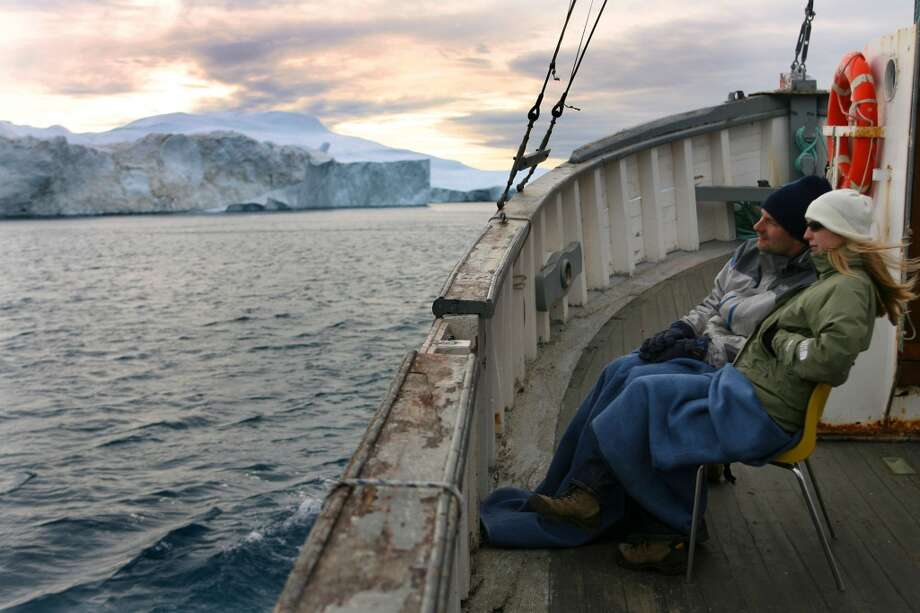 Tourists admire the view of a floating iceberg  in the Jacobshavn Bay on August 26, 2007 near Ilulissat in Greenland.