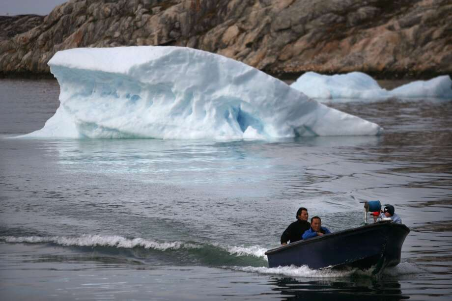 Inuit fishermen sail in their boat August 30, 2007, in the town of Ilulissat  Greenland.