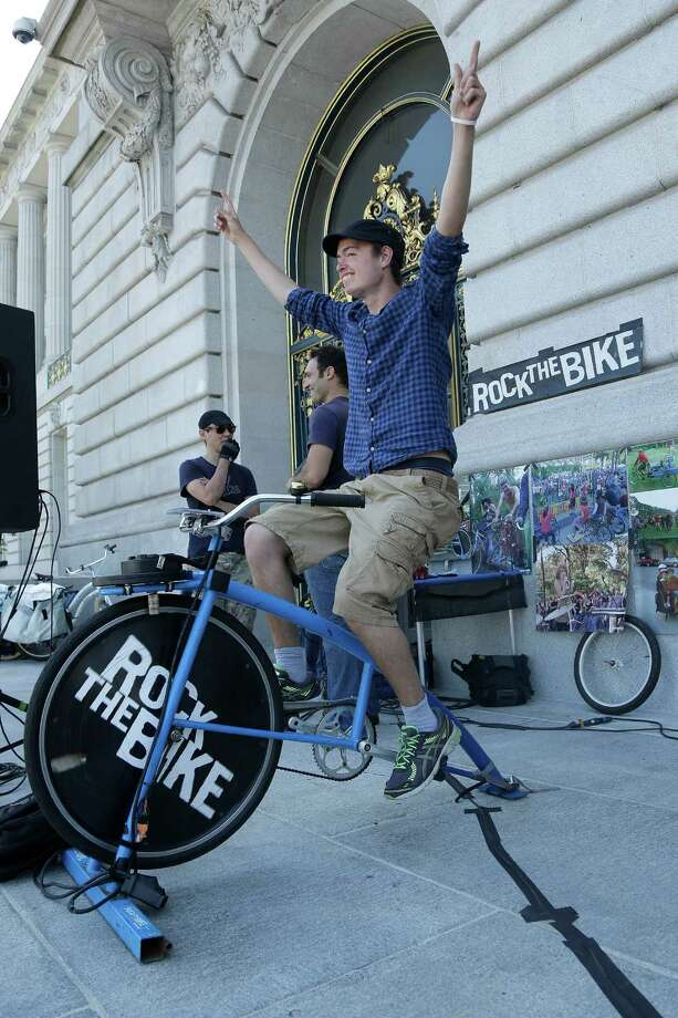 "Jakob von Essen, who came from Sweden to intern with Bay Area Green Tours, gestures toward a crowd as he rides a Rock The Bike ""One Bike/One Speaker,"" a bicycle that generated power for the sound system at rally to support fossil fuel divestment outside of City Hall in San Francisco, Thursday, May 2, 2013. (AP Photo/Jeff Chiu) Photo: Jeff Chiu"