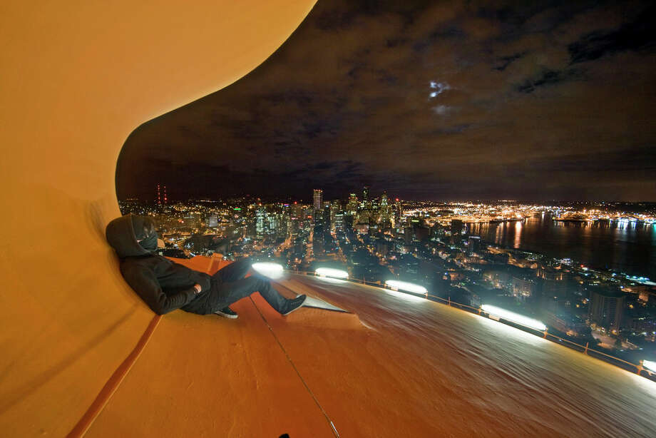 A climber is shown on the curved roof of the Space Needle in this image uploaded to the Internet. / acrophiliac987654321