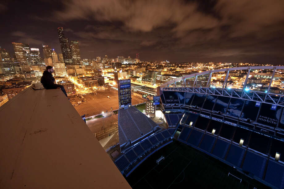 A man sits on the top of the CenturyLink Field arch in this image uploaded to the Internet.