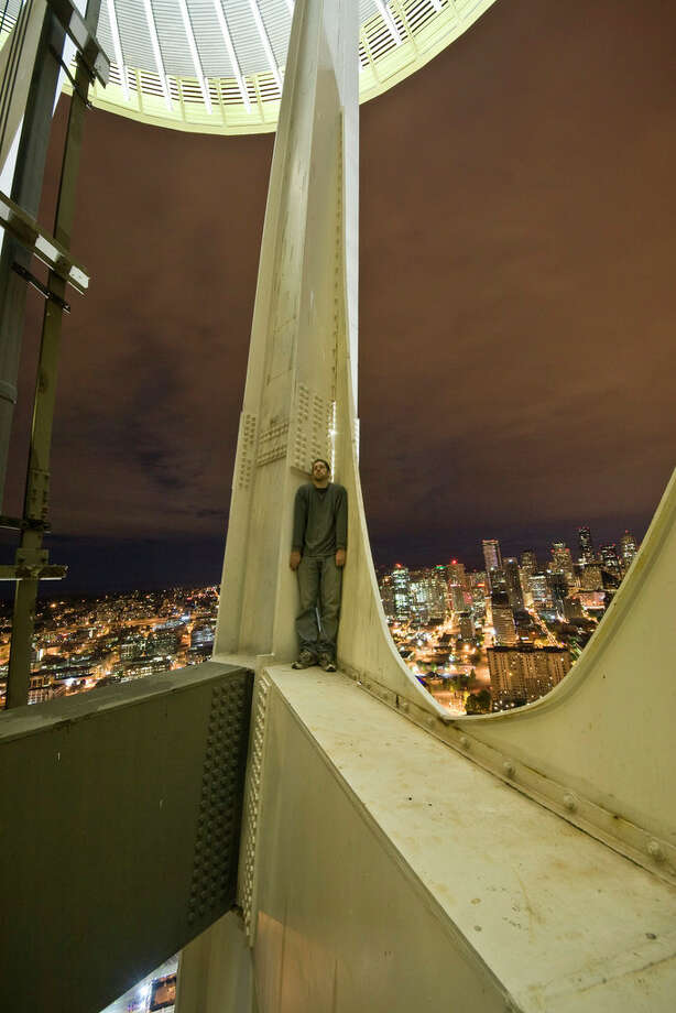 A man stands on the Space Needle in this image uploaded to the Internet. / acrophiliac987654321