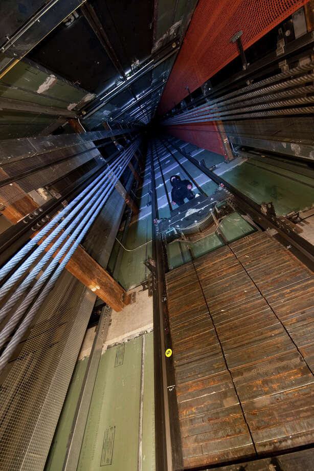 A man rides the counterweight to a skyscraper's elevator in this image uploaded to the Internet.