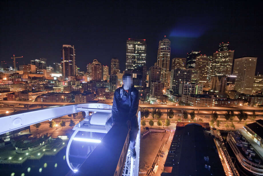 A man sits on the top of Seattle's Great Wheel in this image uploaded to the Internet.