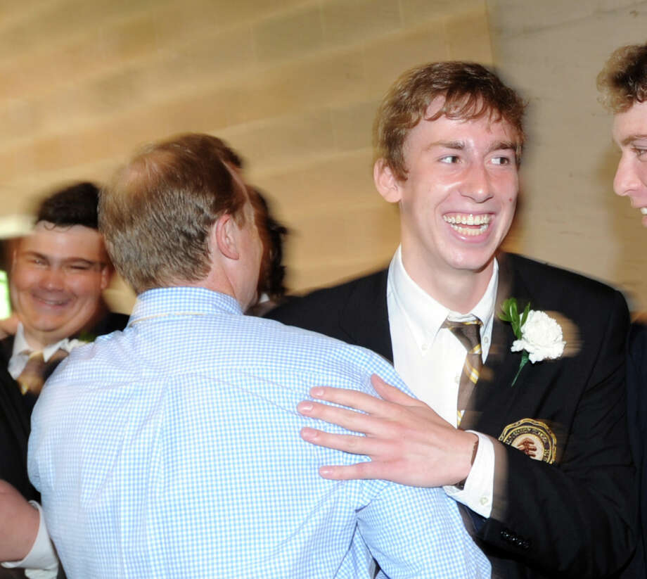 At right, Brunswick School graduating senior, Peter Rogan, 18, of Greenwich, smiles while getting a hug during the Brunswick School Graduation at the school in Greenwich, Wednesday, May 22, 2013. Photo: Bob Luckey / Greenwich Time