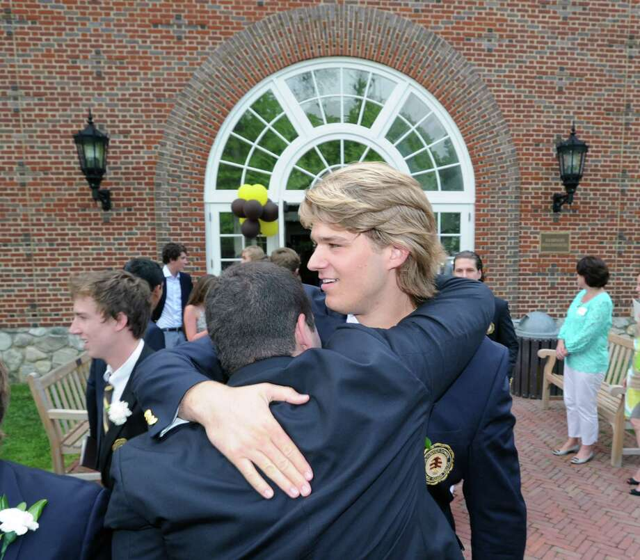 At right, Todd Stafford of Greenwich, pats a fellow graduate on the back at the conclusion of the Brunswick School Graduation at the school in Greenwich, Wednesday, May 22, 2013. Stafford, a star quarterback at Brunswick Schoo,l is heading to the University of Massachusetts, where he will play football. Photo: Bob Luckey / Greenwich Time