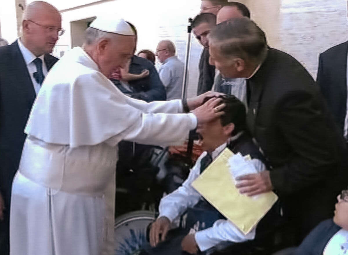 In this image made from video provided by APTN, Pope Francis lays his hands on the head of a young man on Sunday, May 19, 2013, after celebrating Mass in St. Peter's Square. The young man heaved deeply a half-dozen times, convulsed and shook, and then slumped in his wheelchair as Francis prayed over him. The television station of the Italian bishops' conference said it had surveyed exorcists, who agreed Francis either performed an exorcism or a prayer to free the man from the devil. The Vatican was more cautious Tuesday, saying Francis