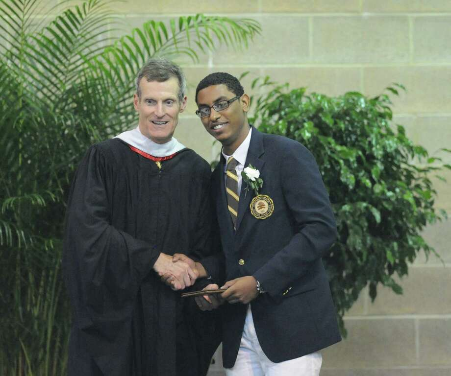 At left, Brunswick School Headmaster, Thomas Philip, shakes the hand of graduating senior, Jordan Reid, of Mount Vernon, N.Y., during the Brunswick School Graduation at the school in Greenwich, Wednesday, May 22, 2013. Photo: Bob Luckey / Greenwich Time
