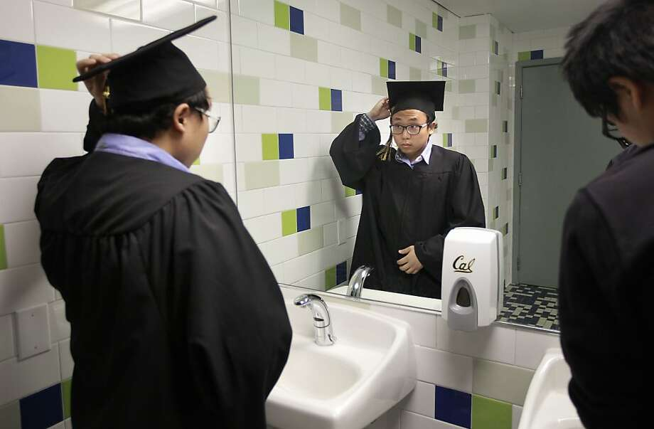 Terrence Park prepares for his UC Berkeley graduation, wearing a gown borrowed from a new program that encourages graduates to donate their gowns for students who can't afford the $50 for a new one. Photo: Michael Macor, The Chronicle