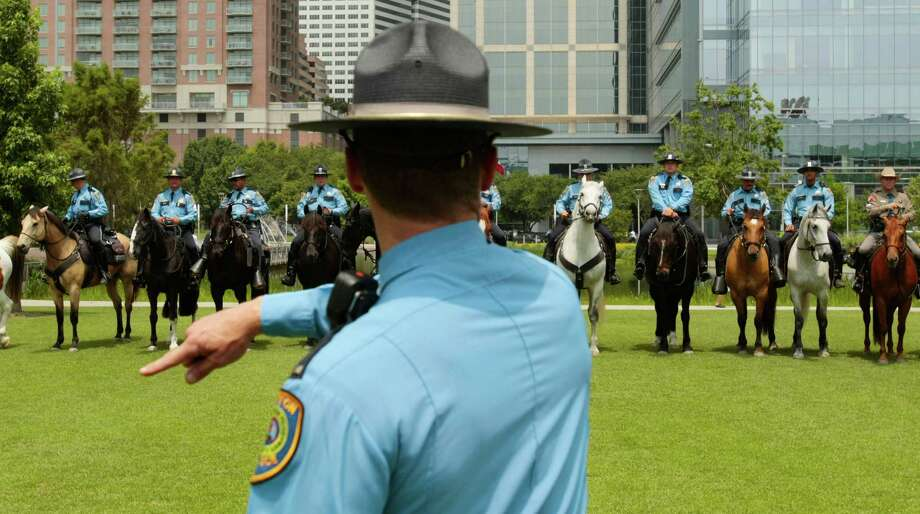 Houston Police Department Mounted Patrol officer Lt. Wallce directs patrol officers for a photo after a graduation ceremony for eight new mounted patrol officers at Discovery Green in Houston. Photo: Billy Smith II, Chronicle / © 2013 Houston Chronicle