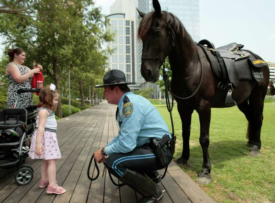 Laura Castellani watches as her daughter, three year-old Melissa, and husband Houston Police Department Mounted Patrol officer Chris Castellani celebrate Chris's graduation from mounted patrol school at Discovery Green. Photo: Billy Smith II, Chronicle / © 2013 Houston Chronicle