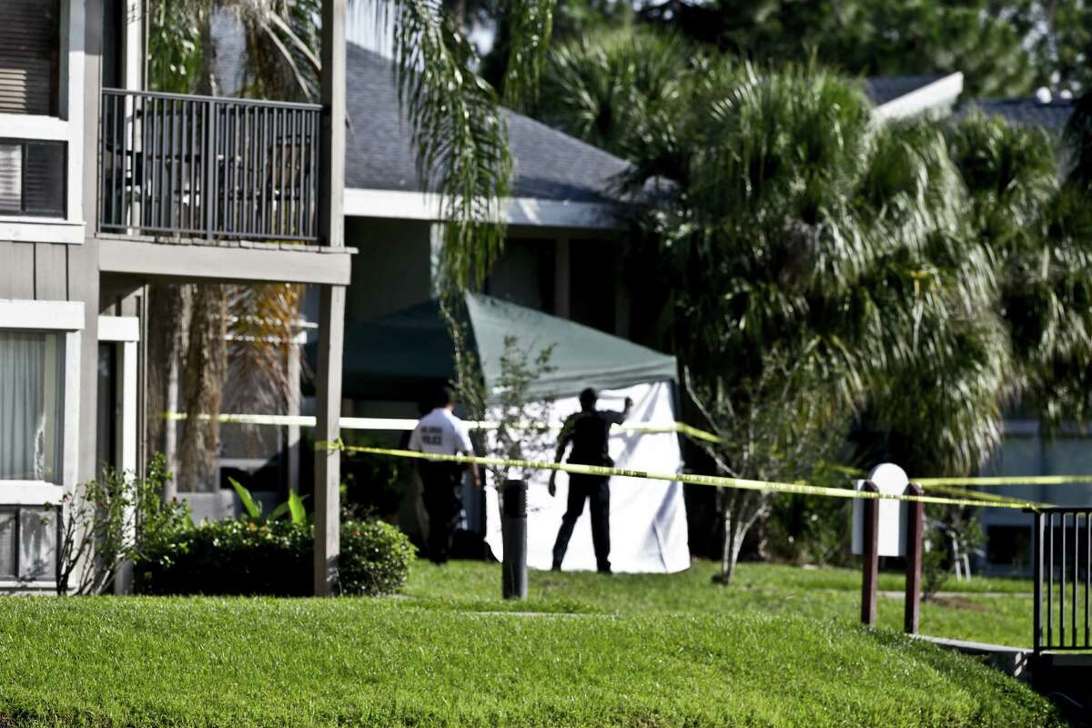 Investigators stand outside an apartment complex where Ibragim Todashev was fatally shot hours after a police team swarmed his home early Wednesday in Orlando, Fla. The FBI says he and the suspects in the bombing of the Boston Marathon were suspects in a triple killing on Sept. 11, 2011.