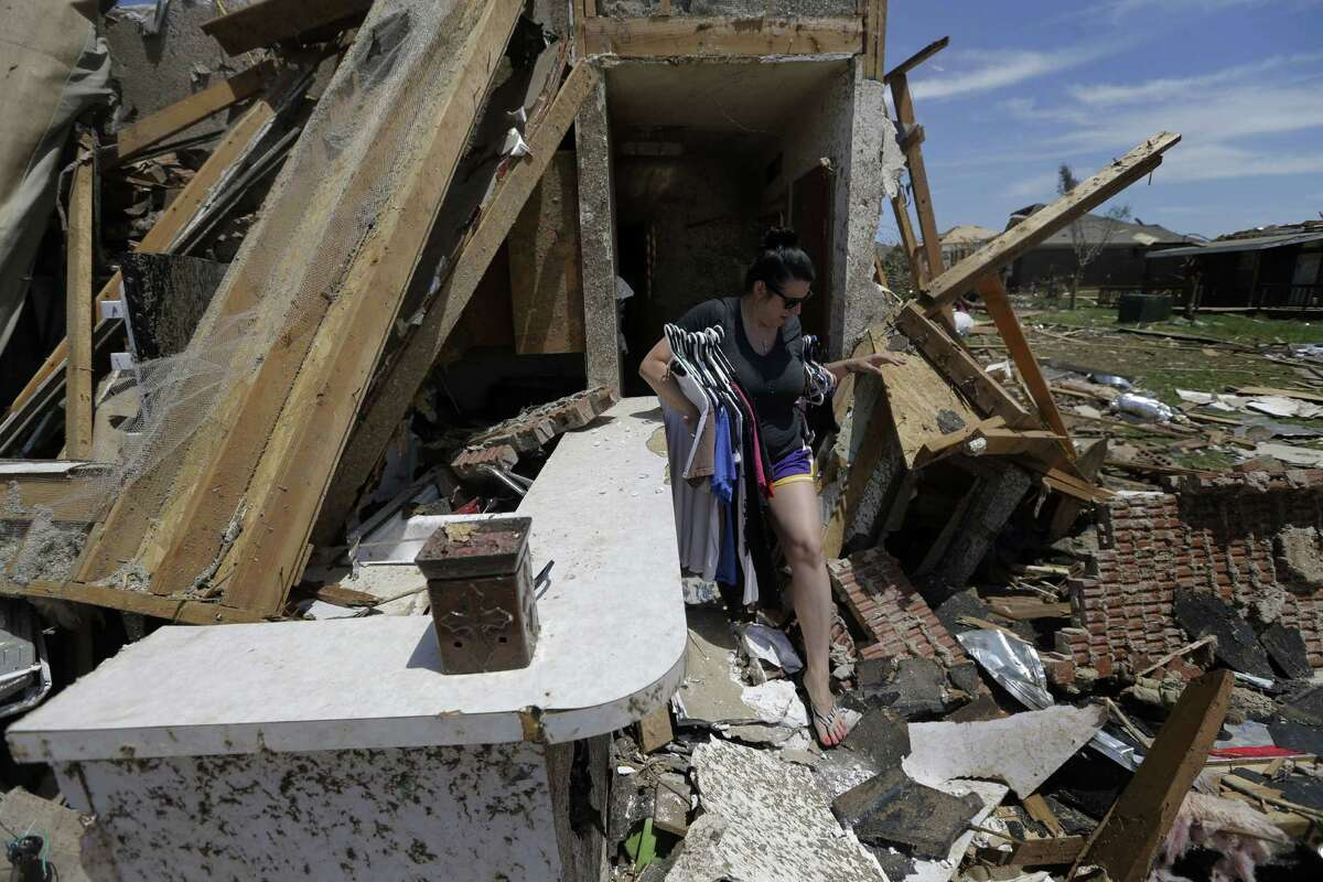 Jessica Leyton salvages clothing on hangers and other items from the bedroom at the home of Kevin and Latisha McElvany in Moore, Okla., on Wednesday.