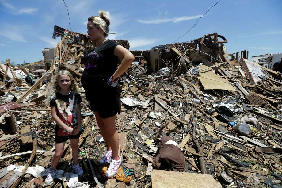 Addison Paul, 7, stands by her mother Leslie as they take a short break from recovery efforts at Paul's tornado damaged home Wednesday, May 22, 2013, in Moore, Oklahoma. (AP Photo/Tony Gutierrez) Photo: Tony Gutierrez