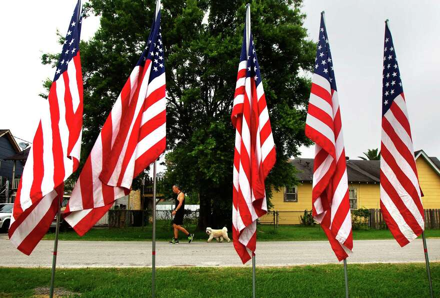 Cliff Ando walks his dog, Maya, amongst a row of American Flags on Norhill, Wednesday, May 22, 2013,