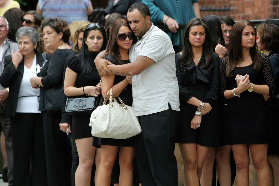 Mourners embrace outside St. Teresa of Avila Church after the funeral service for Andrea Rebello, Wednesday, May 22, 2013 in Sleepy Hollow, N.Y. Rebello, a junior at Hofstra University in Hempstead, N.Y., was shot and killed Friday, May 17, 2013, during a break-in near the college campus.  (AP Photo/Mary Altaffer) Photo: Mary Altaffer