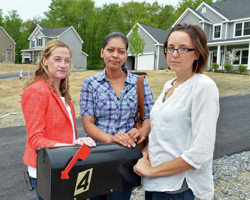 Ridge Wood Drive residents, from left, Lauren Berger, Payal Patel and Ashley Putz outside a home in Halfmoon, N.Y., Wednesday, May 15, 2013. The post office at first declined to provide their new neighborhood with house-by-house mail service. (John Carl D'Annibale / Times Union)