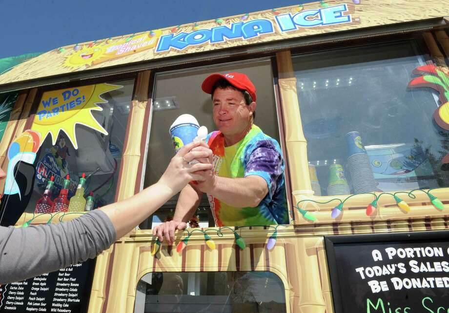 Glen Greco reaches to hand off a cup of ice from his new Kona Ice truck on Thursday, May 2, 2013 in Colonie, N.Y. Greco is continuing Kona Ice?s tradition of donating thousands of dollars each year to local school groups, teams and community organizations.  (Lori Van Buren / Times Union) Photo: Lori Van Buren / 10022234A