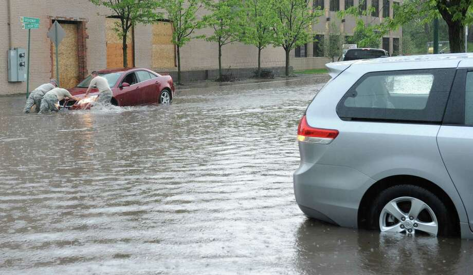 A car is pushed out of a flooded section of Broadway and Clinton St. due to heavy rains on Wednesday, May 22, 2013 in Schenectady, N.Y. (Lori Van Buren / Times Union) Photo: Lori Van Buren