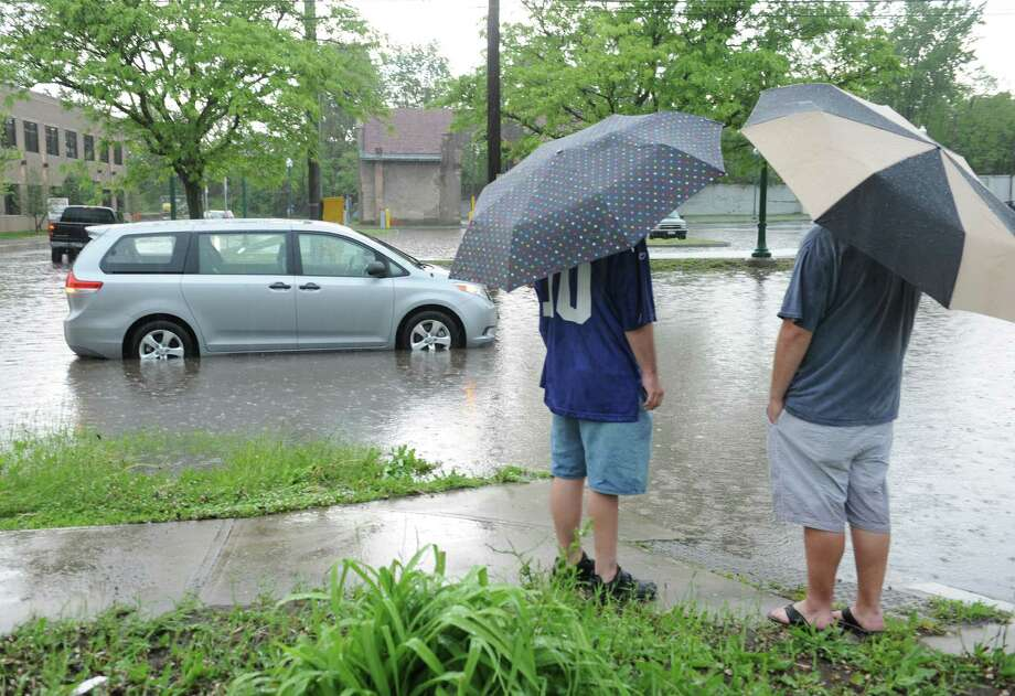 A driver and passenger of a stranded van wait for help at a flooded section of Broadway and Clinton St. on Wednesday, May 22, 2013 in Schenectady, N.Y. Heavy rains cause flash flooding in the area. (Lori Van Buren / Times Union) Photo: Lori Van Buren