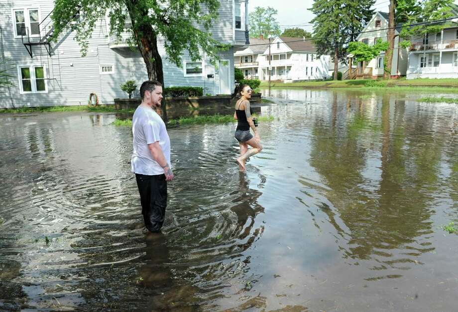 Ken Byers and his fiancee Shelby Countermine wade through the the water on a flooded Guilderland Ave. in front of their home, at left, on Wednesday, May 22, 2013 in Schenectady, N.Y. The flood water, which was caused by a heavy rain storm, reached their front door and flooded their apartment. (Lori Van Buren / Times Union) Photo: Lori Van Buren