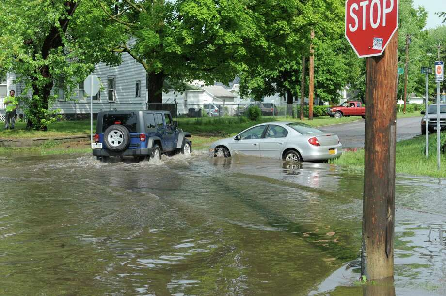 A Jeep makes it's way past a stranded car in a flooded Guilderland Ave. on Wednesday, May 22, 2013 in Schenectady, N.Y.  (Lori Van Buren / Times Union) Photo: Lori Van Buren