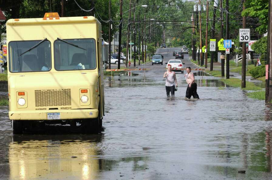 People cross a flooded Guilderland Ave. on Wednesday, May 22, 2013 in Schenectady, N.Y. Heavy rains
