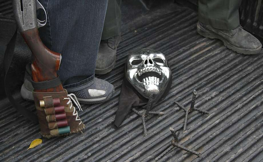 In this May 19, 2013 photo, a mask and spikes for puncturing tires lay next to the feet of armed men from a local self-defense group as they ride in a pick-up truck near the town of La Ruana, Mexico. Self-defense groups started to spring up in February to fight back the Knights Templar drug cartel which is extorting protection payments from cattlemen and lime growers, butchers and even marijuana growers. The federal government sees both the self-defense forces and the cartel as dangerous enemies. (AP Photo/Marco Ugarte) Photo: Marco Ugarte, Associated Press