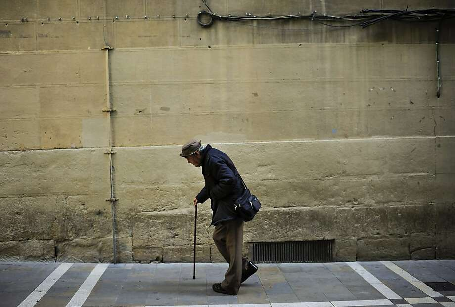 An elderly man goes for a walk aided by a walking-stick, in Pamplona northern Spain on Wednesday, May 22, 2013. (AP Photo/Alvaro Barrientos) Photo: Alvaro Barrientos, Associated Press