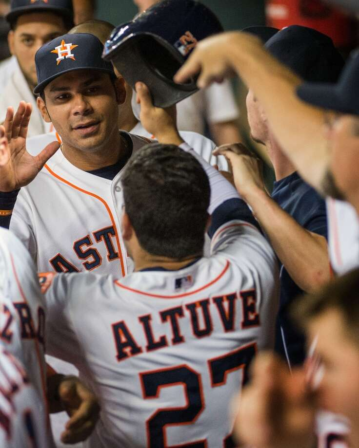 Astros designated hitter Carlos Pena greets second baseman Jose Altuve (27) in the dugout after Altuve scored on a double by Jason Castro during the eighth inning.