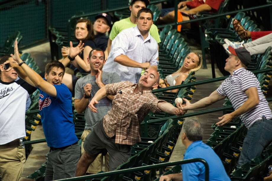 Fans try to catch a foul ball off the bat of Kansas City center fielder Lorenzo Cain during the second inning.